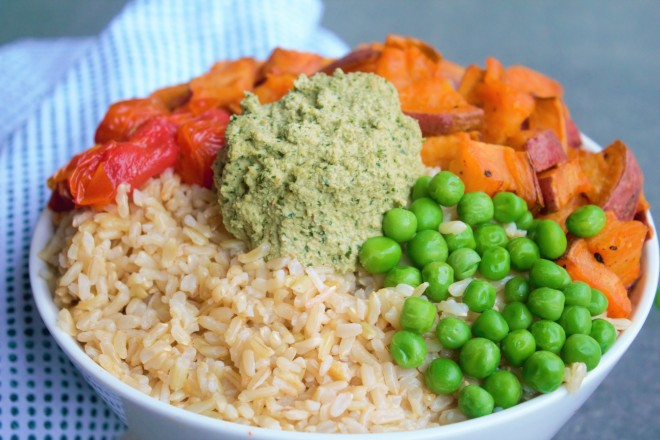 A bowl of brown rice (simmered in broth) topped with steamed peas, roasted tomatoes & sweet potato, and a scoop of cilantro cashew butter.