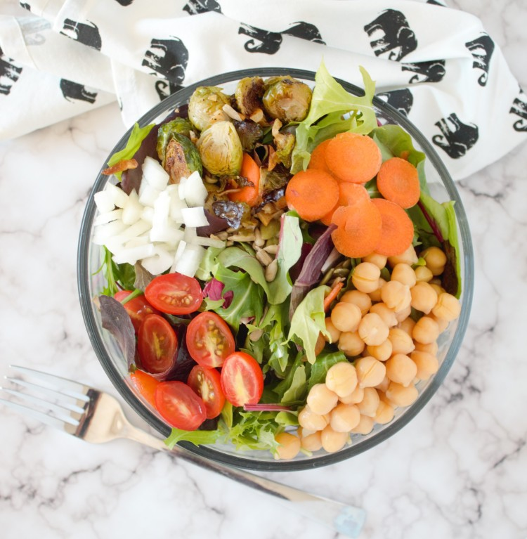 A salad of mixed greens, Brussels sprouts, carrots, tomato, onion, sunflower seeds, and garbanzo beans.