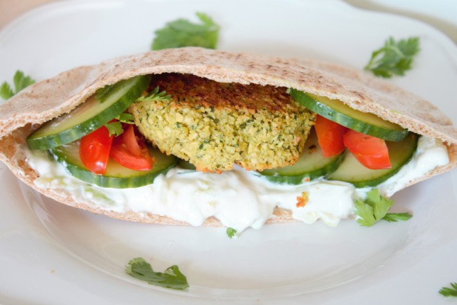 Tzatziki sauce in a sprouted whole grain pita with baked falafel, cucumber slices, and tomato.