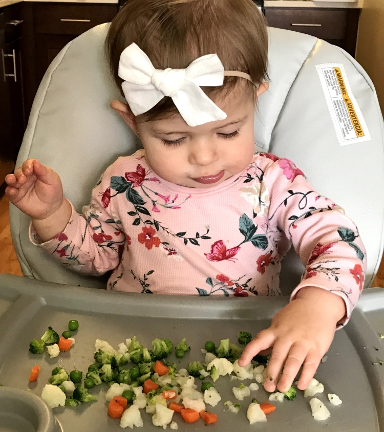 baby eating vegetables (broccoli, peas, carrots, cauliflower)