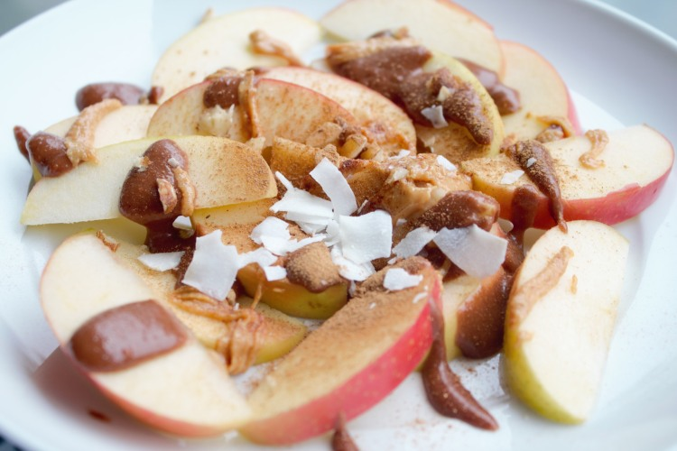 Apple slices topped with homemade peanut butter, cacao hazelnut butter, shredded coconut, and cinnamon.